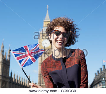 Portrait of smiling woman with British flag in front of Big Ben clocktower - Stock Photo