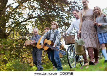 Multi-generation family with guitar and bicycle in apple orchard - Stock Photo