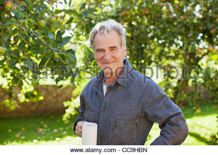Portrait of confident senior man drinking coffee in orchard - Stock Photo