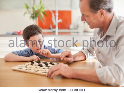 Grandfather and grandson playing checkers - Stock Photo