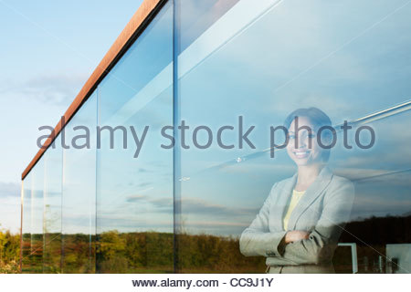 Portrait of smiling businesswoman with arms crossed in office window - Stock Photo