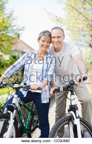 Portrait of smiling senior couple on bicycles - Stock Photo
