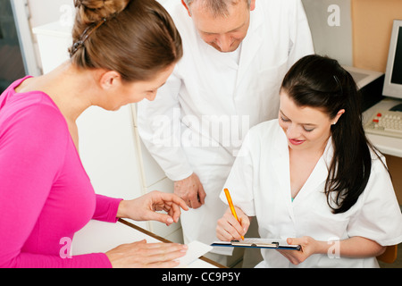Patient in reception area of office of doctor or dentist, handing her health insurance card over the counter to - Stock Photo