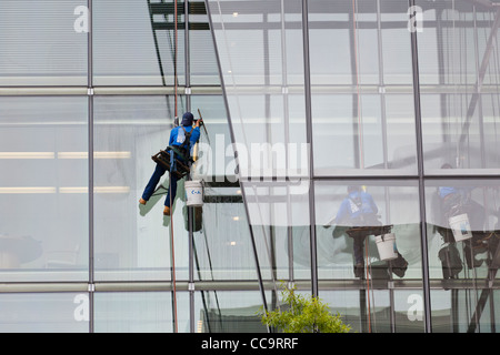 High rise window cleaner  sitting in a bosun's chair - Stock Photo