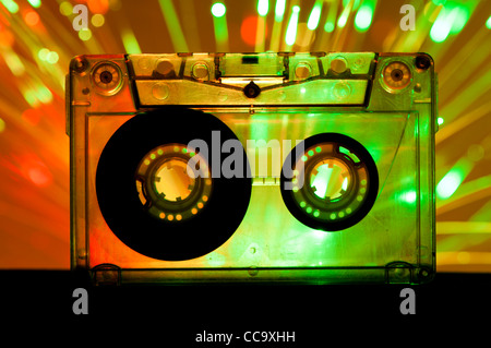 Transparent Cassette tape and green orange color disco lights background - Stock Photo