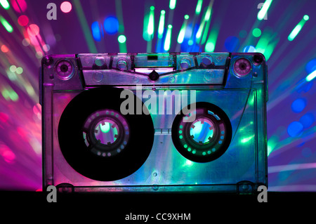 Transparent Cassette tape and blue pink color disco light background - Stock Photo