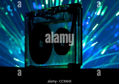 Transparent Cassette tape and blue color disco light background - Stock Photo