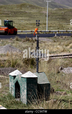 Roadside grave of accident victim, road resurfacing in background, road between Cusco and Puno , Peru - Stock Photo