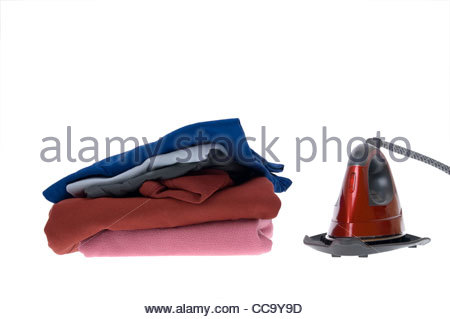 Stack of ironed clothes with red steam electric iron - Stock Photo