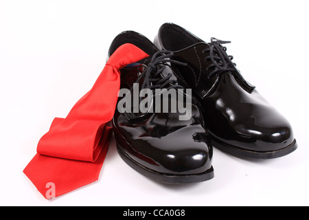 Mens shiny lace up formal black shoes with red tie on a white background - Stock Photo