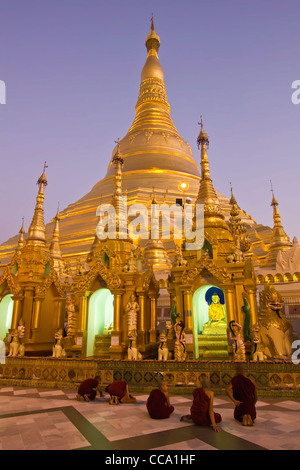 Novice Monks Praying in front of the Main Stupa of the Shwedagon Paya (Pagoda) at Dusk   Yangon (Rangoon)   Myanmar - Stock Photo