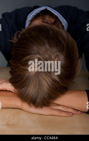 Portrait of tired man laying face down on table at his office - Stock Photo