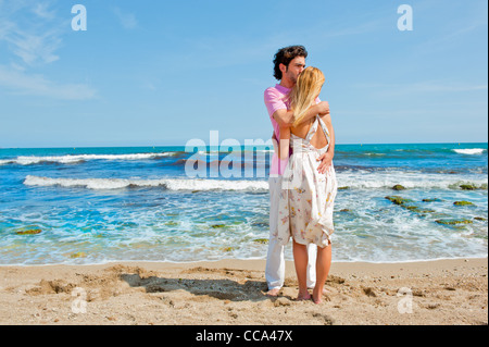 Portrait of young couple in love embracing at beach and enjoying time being together - Stock Photo