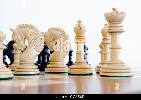 Chess pieces on wood board, black and white - Stock Photo