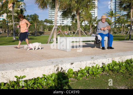 Elderly man sitting on a bench in the sun as a woman walks past with her dog - Stock Photo
