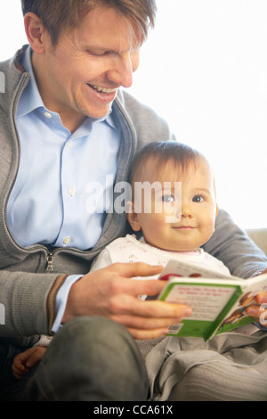 Father Reading Picture Book For Baby Daughter - Stock Photo