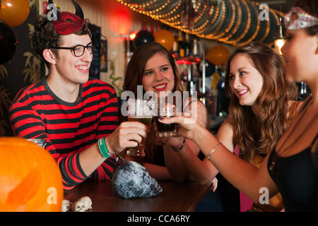 Young friends toasting drinks in bar - Stock Photo