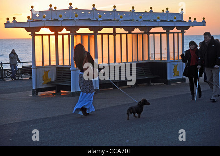 People out walking past a shelter during a spectacular sunset along Hove seafront Sussex UK - Stock Photo