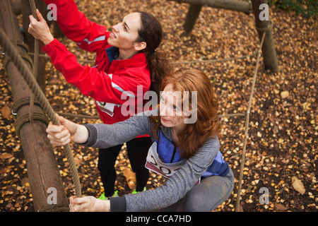 Young women climbing rope on assualt course - Stock Photo