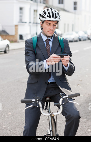 Mid adult businessman using cellphone to text on bicycle - Stock Photo