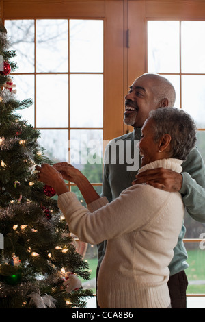 Mature couple decorating Christmas tree - Stock Photo