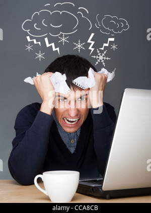 Closeup of a young angry business man having a stress. Headache. Against gray background - Stock Photo