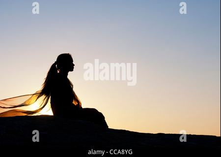 Indian girl sitting all alone on a rock at sunset. Silhouette. Andhra Pradesh, India - Stock Photo