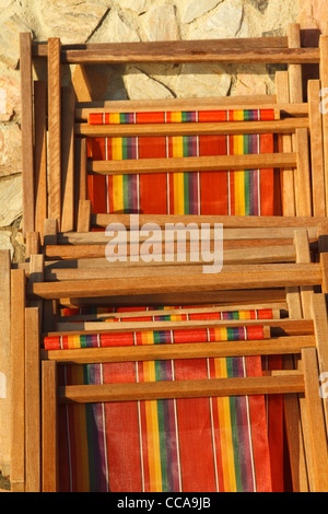 Wooden striped deck chairs leaning against a stone wall in the sun - Stock Photo