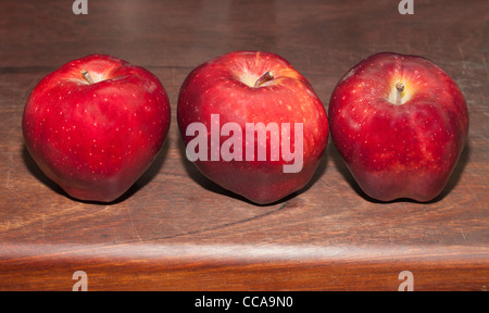Red Delicious apples on a wooden cutting board - Stock Photo