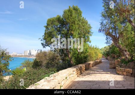 Narrow paved promenade in Yafo (Jaffa) with view on modern buildings of Tel Aviv along Mediterranean sea coastline - Stock Photo