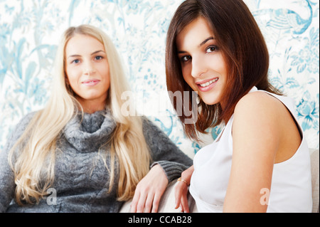 Two young women friends chatting at home. One showing to another her proposal ring - Stock Photo