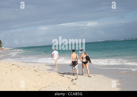 Two girls and man walking away on a sand beach - Stock Photo