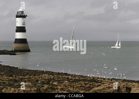 Two racing yachts passing Trwyn Du lighthouse at Penmon, Anglesey, North Wales, UK - Stock Photo