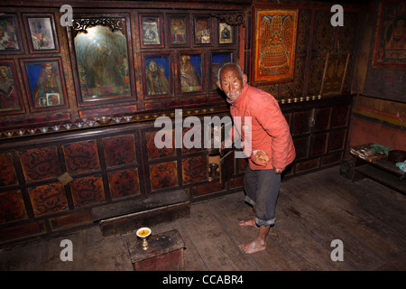 India, Arunachal Pradesh, Tawang, Lhou village, house interior elder Monpa man at antique prayer room cabinet - Stock Photo