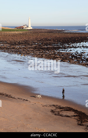 Man walking Dalmation dog on otherwise empty beach with St Mary's lighthouse in the background north east England - Stock Photo