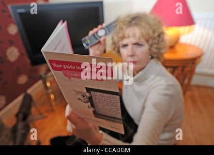 Middle aged woman reads the instruction leaflet for the Meridian TV area from digitaluk on the digital switchover - Stock Photo