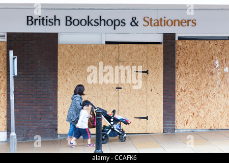 Woman with a child pushes a buggy past a boarded-up shop. - Stock Photo