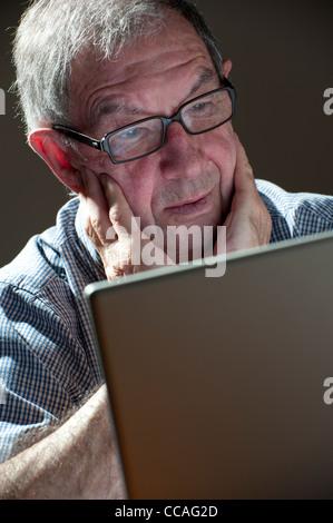 senior male using laptop computer - Stock Photo