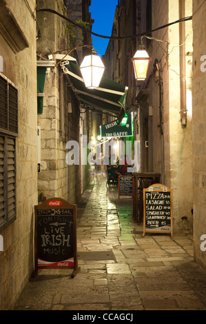Narrow alley in Dubrovnik (Croatia) during nighttime. People sitting at the table and eating in the background - Stock Photo