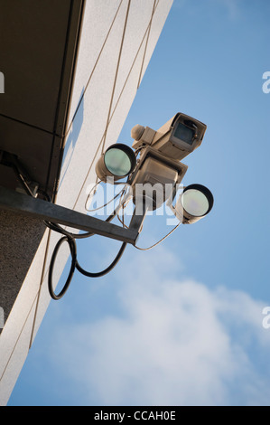 A CCTV camera attached to a building on a bright and clear sky day. - Stock Photo