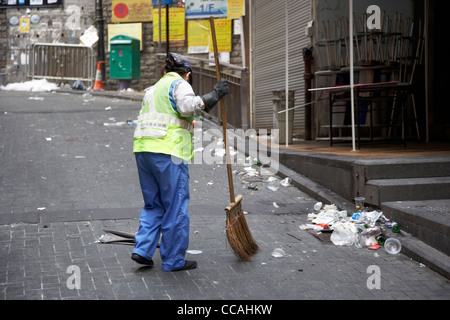 female street cleaner brushing streets with broom early morning in lan kwai fong hong kong hksar china asia - Stock Photo