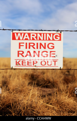 Warning Firing Range Keep Out sign hanging on a barbed wire fence. - Stock Photo