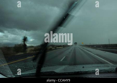 Traffic moves through rain on Interstate 10 in Benson, Arizona, USA. - Stock Photo