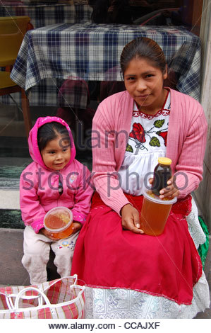 Street scene Mexican mother and daughter selling honey to passerby looking at camera. Social issues single parenting - Stock Photo