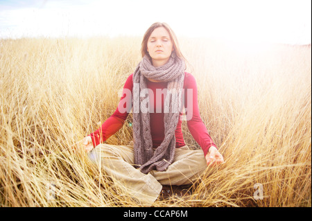 Beautiful young woman meditating in peace radiating light in a long grass field - Stock Photo