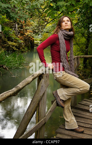 Beautiful young woman contemplating the sky surrounded by lush green vegetation leaning on a wooden bridge over - Stock Photo