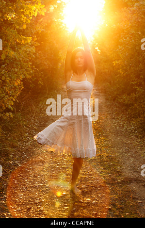 Beautiful young woman balancing on one leg meditating with hands above her head embracing the golden light of the - Stock Photo