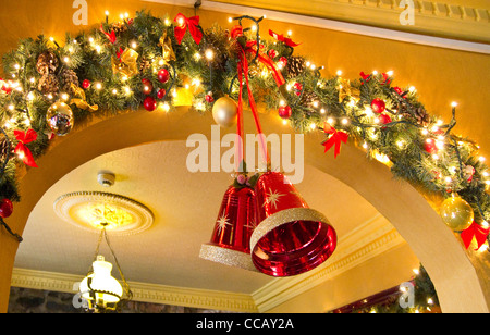Bells and fairy lights as part of the Christmas decorations in an Irish pub. - Stock Photo