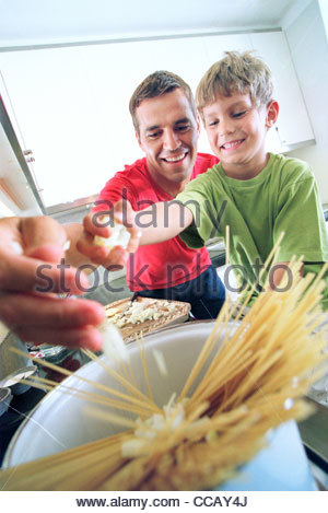 Father and son cooking spaghetti together - Stock Photo