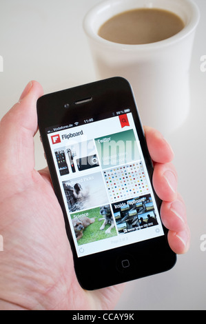 Using Flipboard social networking app on an iPhone 4g smart phone - Stock Photo